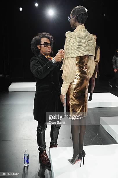 Designer David Tlale and a model prepare at the David Tlale Sun Fall 2013 fashion show presentation during MercedesBenz Fashion Week at The Box at...