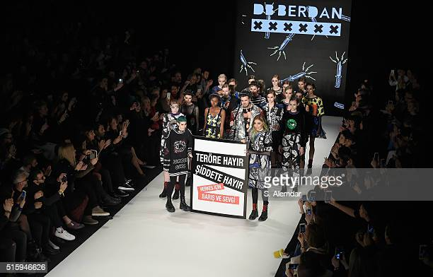 Designer Deniz Berdan and models display a banner against terrorism and violence at the DB Berdan show during the MercedesBenz Fashion Week Istanbul...