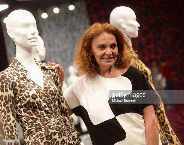 Designer Diane von Furstenberg poses for photographers in front of her collection of Wrap Dresses during the press conference for the Journey of A...
