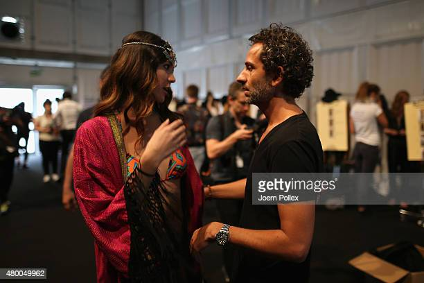 Designer Dimitrios Panagiotopoulos talks to a model backstage ahead of the Dimitri show during the Mercedes-Benz Fashion Week Berlin Spring/Summer...