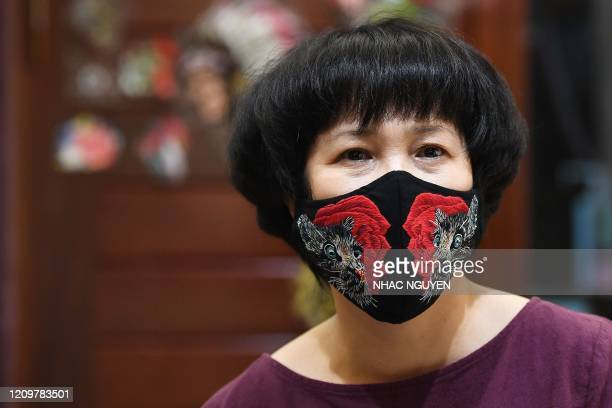 Designer Do Quyen Hoa poses wearing her colourful handembroidered face mask creation used as a preventive measure against the spread of the COVID19...