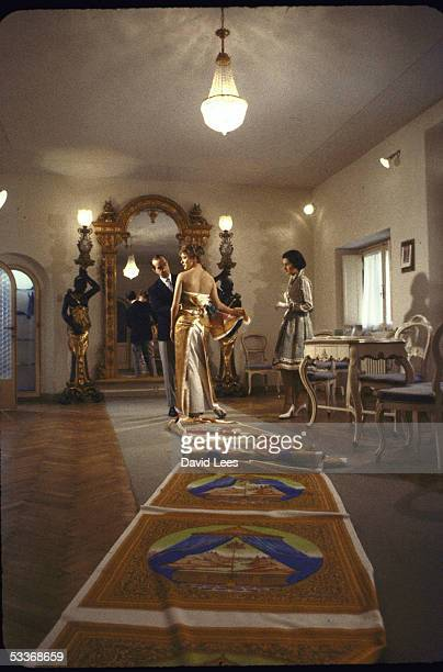 Designer Emilio Pucci, with model, working on elegant evening gown in his palazzo showroom.