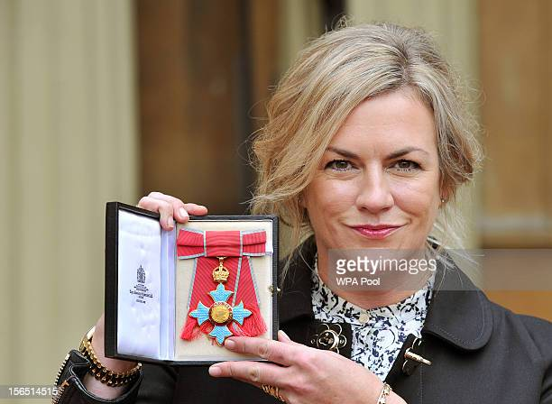 Designer Emma Hill proudly holds her Commander of the British Empire after it was presented to her by Queen Elizabeth II at the Investiture ceremony...
