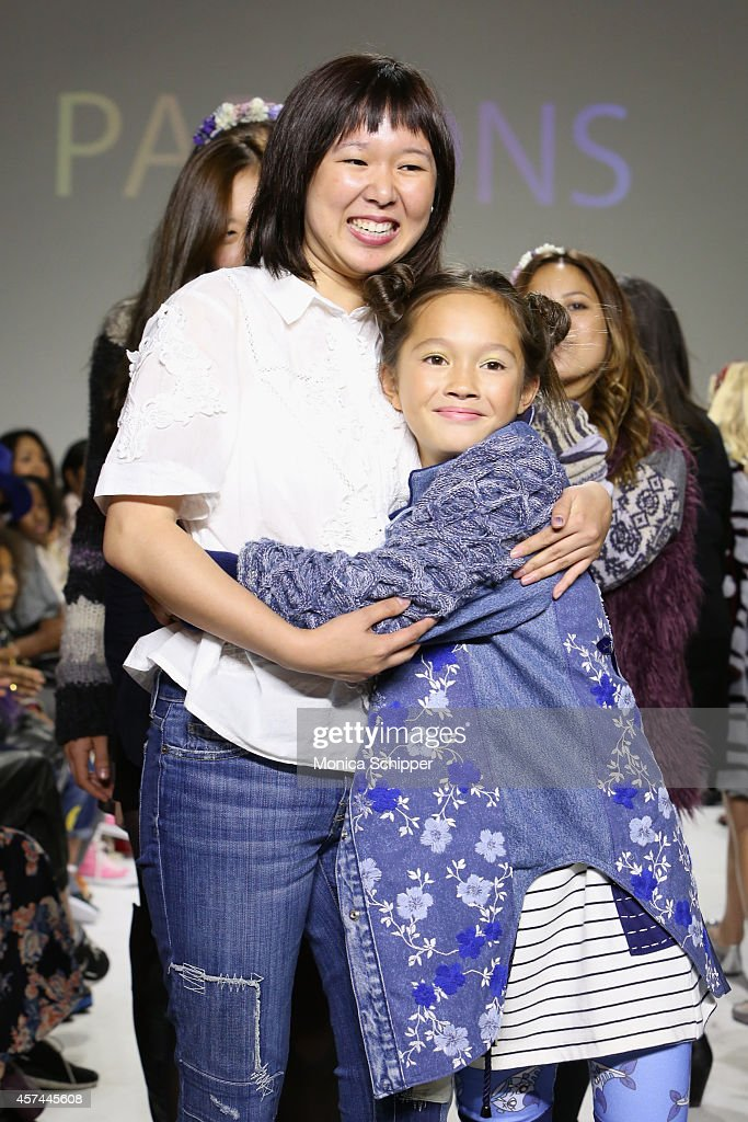 Designer Erica Kim (L) walks the runway with a model during the Parsons preview at petitePARADE / Kids Fashion Week at Bathhouse Studios on October 18, 2014 in New York City.