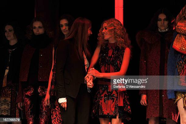 Designer Eva Cavalli is congratulated by model Georgia May Jagger and her other models as she acknowledges the applause of the audience after the...