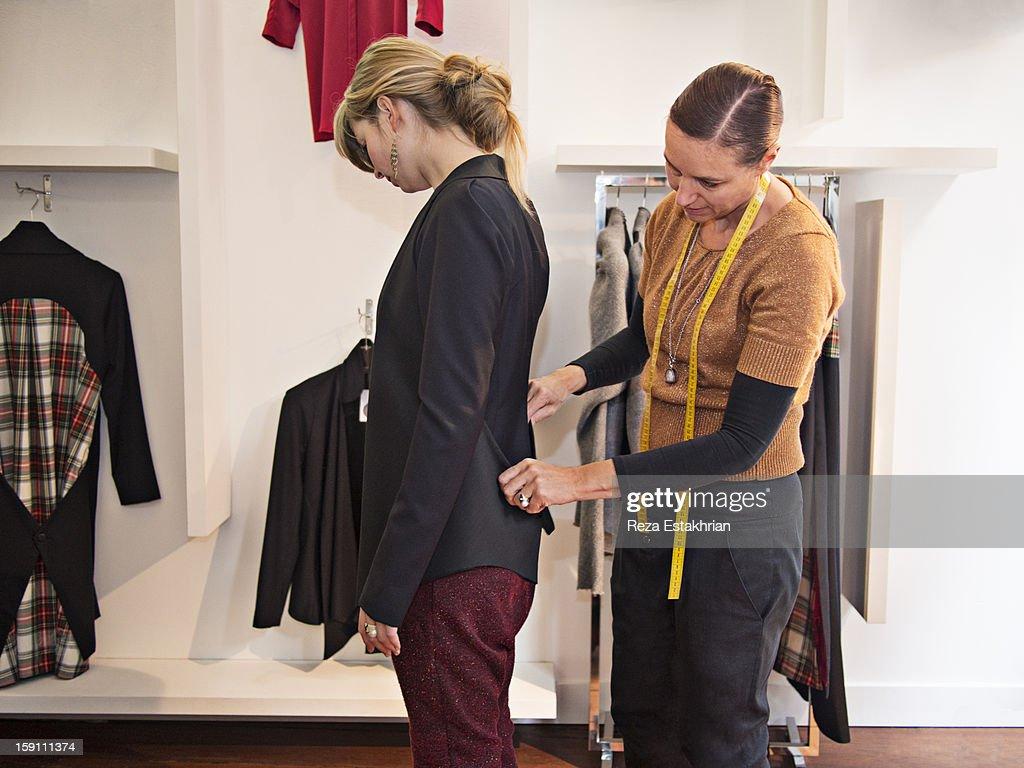Designer fits garment on customer : Stock Photo