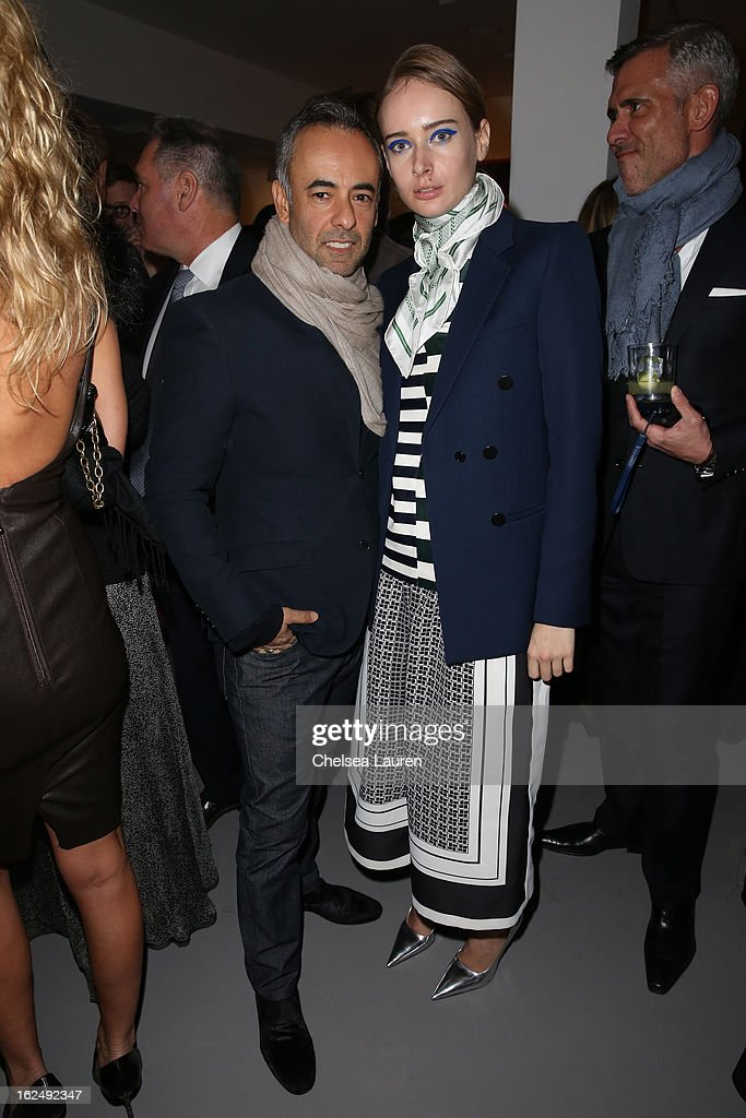 Designer Francisco Costa (L) and Olga Sorokina visit the Mario Testino opening at PRISM during Academy Awards week on February 23, 2013 in Los Angeles, California.