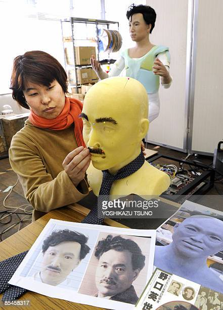 A designer from Japan's robot maker Kokoro puts a eyebrows and a facial hair on a humanoid robot resembling prominent Japanese doctor and...