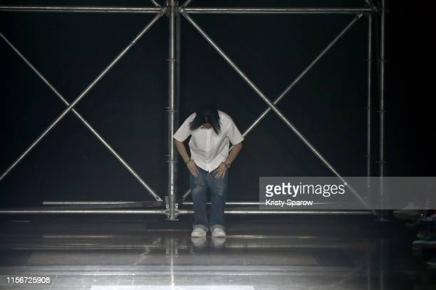 Designer Fumito Ganryu greets the crowd during the Fumito Ganryu Menswear Spring Summer 2020 show as part of Paris Fashion Week on June 18, 2019 in...