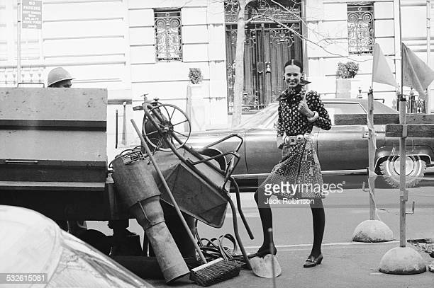 Designer Gloria Vanderbilt stands next to a construction site on a street, New York, New York, 20th century.