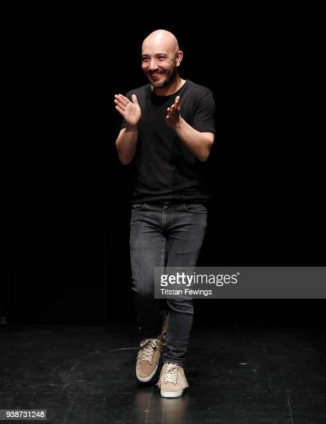 Designer Gokhan Yavas acknowledges the applause of the audience after his show during MercedesBenz Fashion Week Istanbul at the Zorlu Performance...