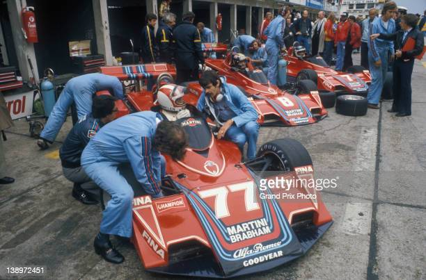Designer Gordon Murray kneels beside Rolf Stommelen in the as Carlos Pace and Carlos Reutemann sitting aboard their Martini Racing Brabham BT45 Alfa...