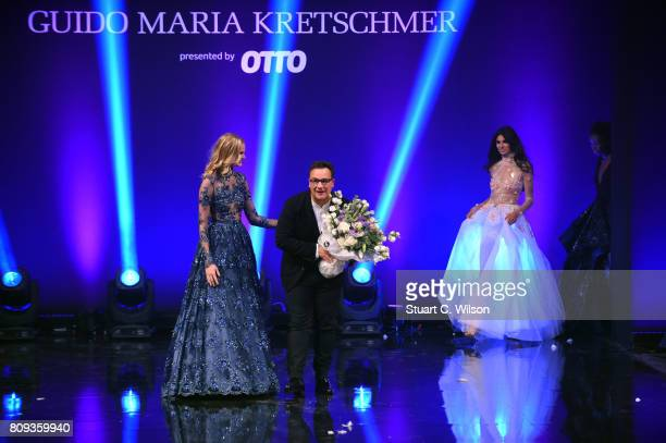 Designer Guido Maria Kretschmer and models acknowledge the applause of the audience the runway during the Guido Maria Kretschmer Fashion Show...