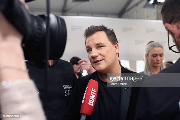 Designer Guido Maria Kretschmer is interviewed before his show during the MercedesBenz Fashion Week Berlin Autumn/Winter 2016 at Brandenburg Gate on...