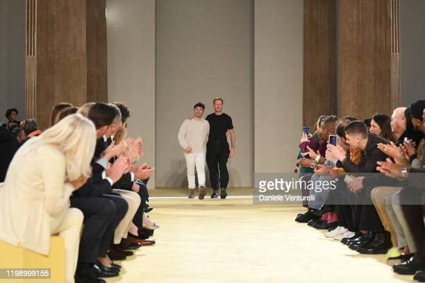 Designer Guillaume Meilland and Paul Andrew acknowledge the applause of the audience after the runway at the Salvatore Ferragamo fashion show on...