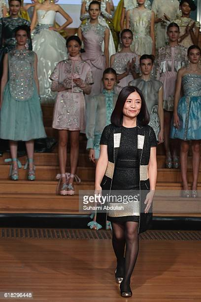 Designer Guo Pei greets the audience at the end of her Spring/Summer 2016 'Courtyard' Collection showcase at Singapore Fashion Week 2016 at the...