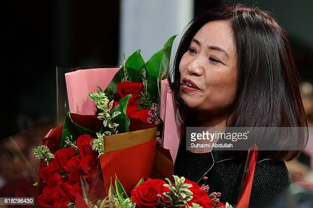 Designer Guo Pei receives bouquet of flowers at the end of her Spring/Summer 2016 'Courtyard' Collection showcase at Singapore Fashion Week 2016 at...