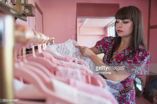 designer hanging garment on fashion collection clothes rack - fashion collection stock pictures, royalty-free photos & images