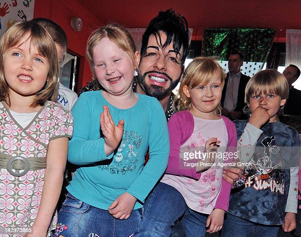 Designer Harald Gloeoeckler poses with children after he handed over a 5000 euro cheque to the 'Deutsches Kinderhilfswerk' in a Kindergarden in...