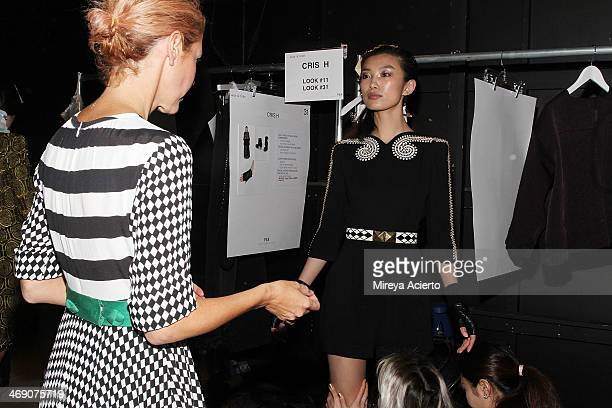 Designer Heidi Middleton dresses a model backstage at the Sass Bide fashion show during MercedesBenz Fashion Week Fall 2014 at The Waterfront on...