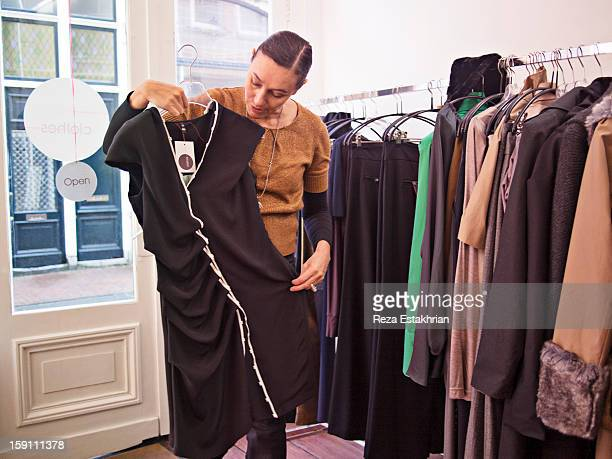 Designer holds up garment