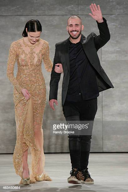 Designer Idan Cohen walks the runway with a model at the Idan Cohen Fashion Show during Mercedes-Benz Fashion Week Fall 2015 at The Pavilion at...