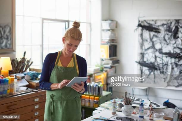 Designer in studio looking at digital tablet