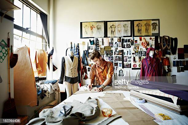 designer in studio measuring pant width - fashion designer stock photos and pictures