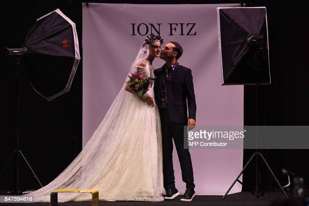 Designer Ion Fiz kisses a model after the presentation of his Spring/Summer 2018 collection during the Madrid Fashion Week in Madrid on September 15...