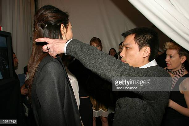 Designer Jeffrey Chow helps a model get ready backstage at the Jeffrey Chow Fall 2004 during Olympus Fashion Week February 12 2004 in New York City