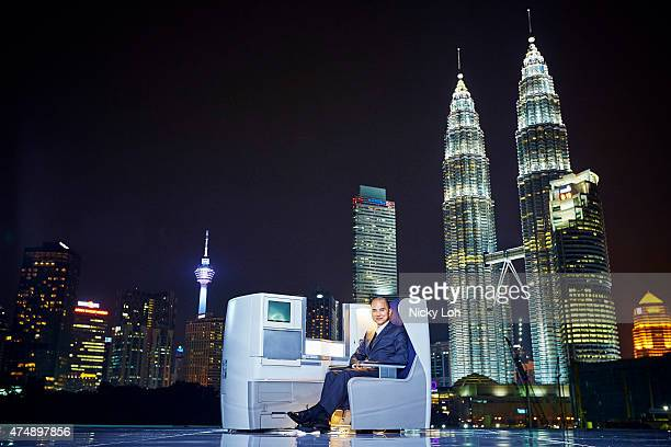 Designer Jimmy Choo relaxes in a British Airways' Club World business cabin seat in front of the Petronas Twin Towers on May 27, 2015 in Kuala...