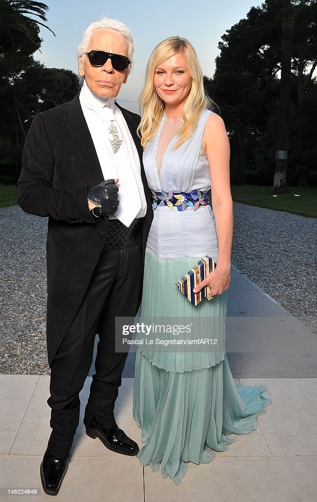 Designer Karl Lagerfeld and actress Kirsten Dunst arrive at the 2012 amfAR's Cinema Against AIDS during the 65th Annual Cannes Film Festival at Hotel Du Cap on May 24, 2012 in Cap D'Antibes, France.