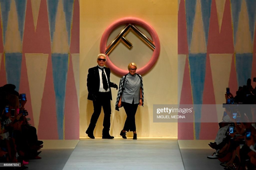Designer Karl Lagerfeld (L) and Silvia Venturini Fendi greet the audience at the end of the show for fashion house Fendi during the Women's Spring/Summer 2018 fashion shows in Milan, on September 21, 2017. / AFP PHOTO / Miguel MEDINA