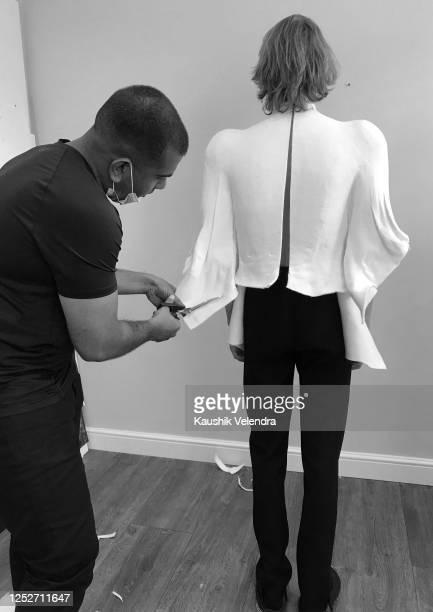 Designer Kaushik Velendra dresses a model Aduring the Kaushik Velendra #LFWRest presentation during London Fashion Week on June 10 2020 in London...