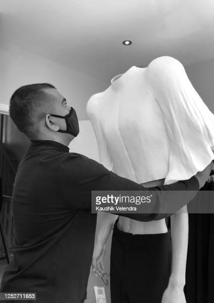 Designer Kaushik Velendra dresses a model during the Kaushik Velendra #LFWRest presentation during London Fashion Week on June 10 2020 in London...