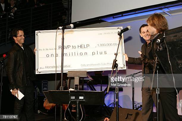 "Designer Kenneth Cole, Bernd Beetz, CEO of Coty present a check to Jon Bon Jovi on stage at Kenneth Cole's ""R.S.V.P. To HELP"" benefit hosted by..."