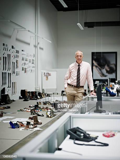 Designer leaning on desk in office