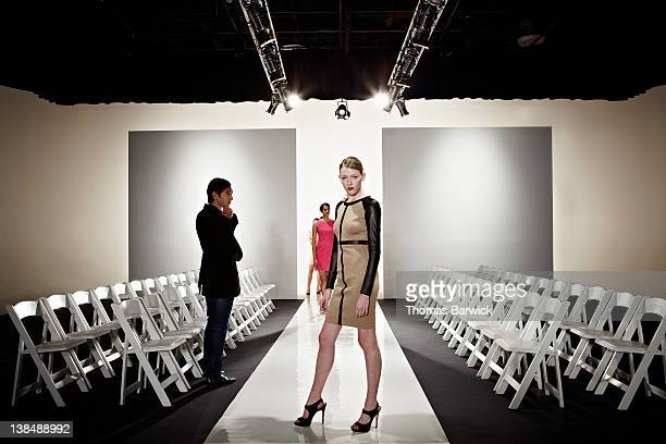 designer looking at model practicing on catwalk - fashion show stock pictures, royalty-free photos & images