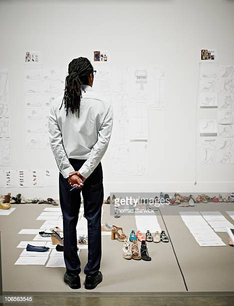 Designer looking at shoe design plans on wall