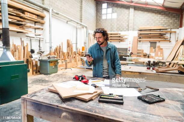 designer looking at smartphone while working in a furniture factory - schreiner stock-fotos und bilder