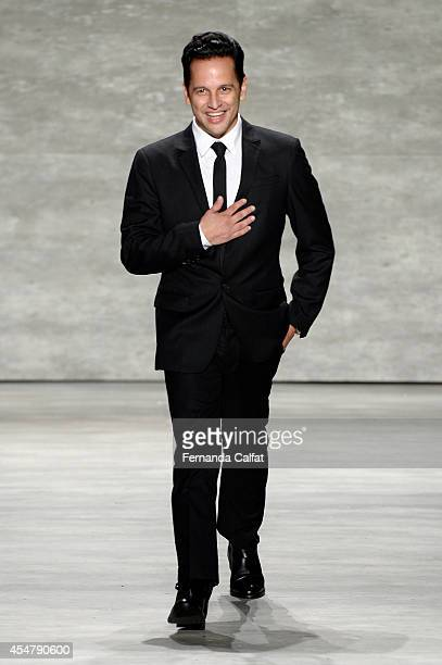 Designer Luis Antonio walks the runway at the Luis Antonio fashion show during Mercedes-Benz Fashion Week Spring 2015 at The Pavilion at Lincoln...