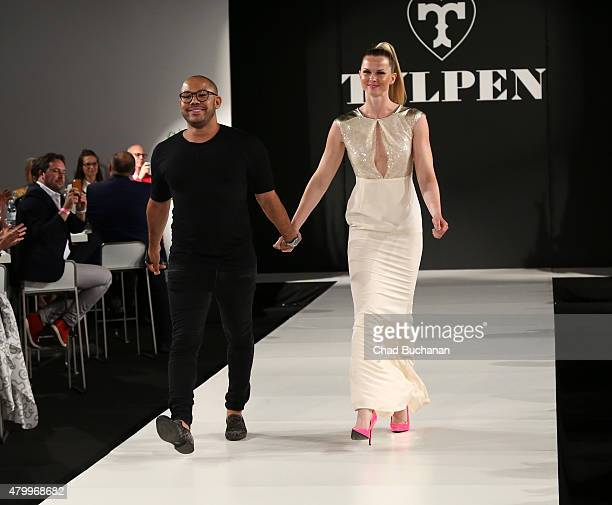 Designer Manuel Kirchner and a model walk the runway at TULPEN DESIGN by Manuel Kirchner fashion dinner on July 8 2015 in Berlin Germany