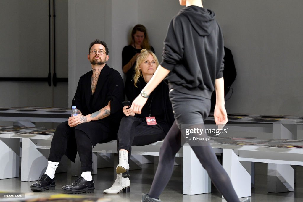 Designer Marcel Ostertag (L) and a model prepare backstage for Marcel Ostertag front row during New York Fashion Week: The Shows at Gallery II at Spring Studios on February 14, 2018 in New York City.