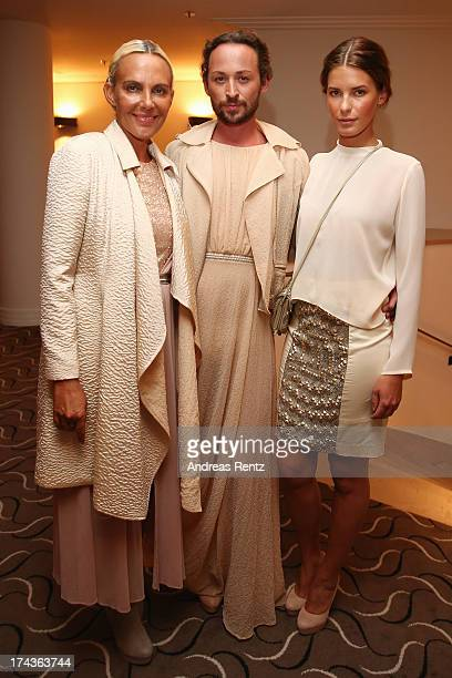 Designer Marcel Ostertag and models Natascha Ochsenknecht and Julia Trainer prepare backstage prior to the Marcel Ostertag fashion show at Charles...