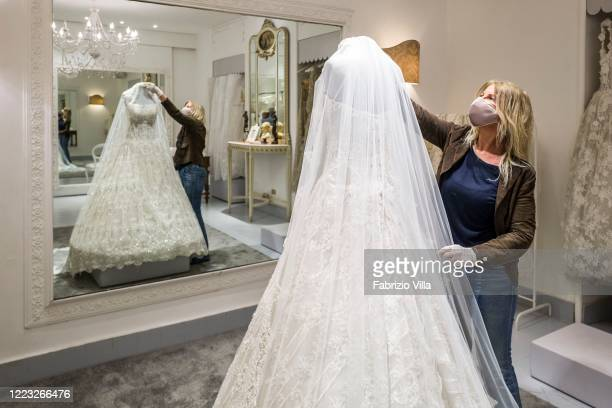 Designer Mariella Gennarino with a mask and protective gloves looks at a mannequin with a wedding dress just made in her atelier in Catania open...