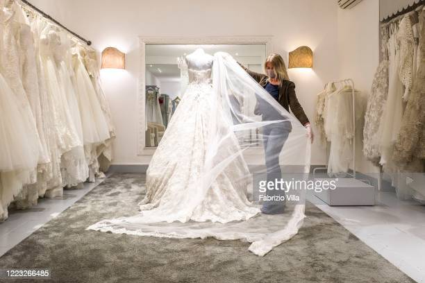 Designer Mariella Gennarino with mask and protective gloves looks at a mannequin with a wedding dress just made in her atelier in Catania open again...