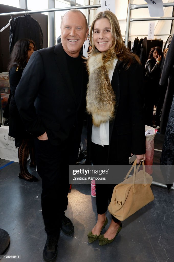 Designer Michael Kors (L) and director of style and image at Estee Lauder Aerin Lauder prepares backstage at the Michael Kors fashion show during Mercedes-Benz Fashion Week Fall 2014 at Spring Studios on February 12, 2014 in New York City.