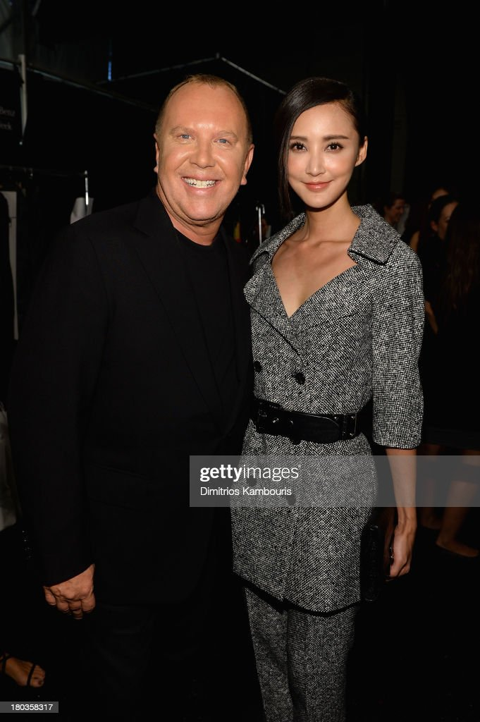 Designer Michael Kors and model Chi-ling Lin pose backstage at the Michael Kors fashion show during Mercedes-Benz Fashion Week Spring 2014 at The Theatre at Lincoln Center on September 11, 2013 in New York City.