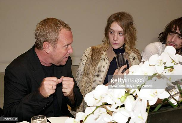 Designer Michael Kors puts up his dukes perhaps in anticipation of delivering a punch line as he talks to actress Chloe Sevigny at a luncheon showing...