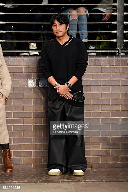 Designer Mihara Yasuhiro salutes the crowd following the Maison MIHARA YASUHIRO show during London Fashion Week Men's January 2017 collections at...